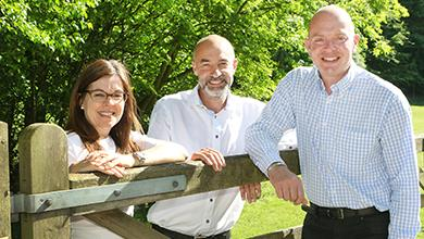 Paul Jones (right) celebrates his new role as Chairman of Marketing Peak District & Derbyshire with outgoing Chairman Paul Roden and Managing Director Jo Dilley at The Camping and Caravanning Club's Hayfield campsite.