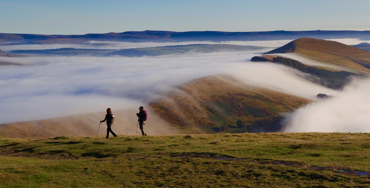 Two people walking on Mam Tor in the Peak District as clouds roll over the hills.