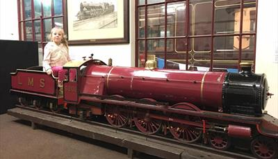 A young visitor sits on a miniature train in the West Shed Museum