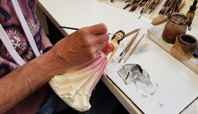 A ceramic artist hand painting a china figurine lady