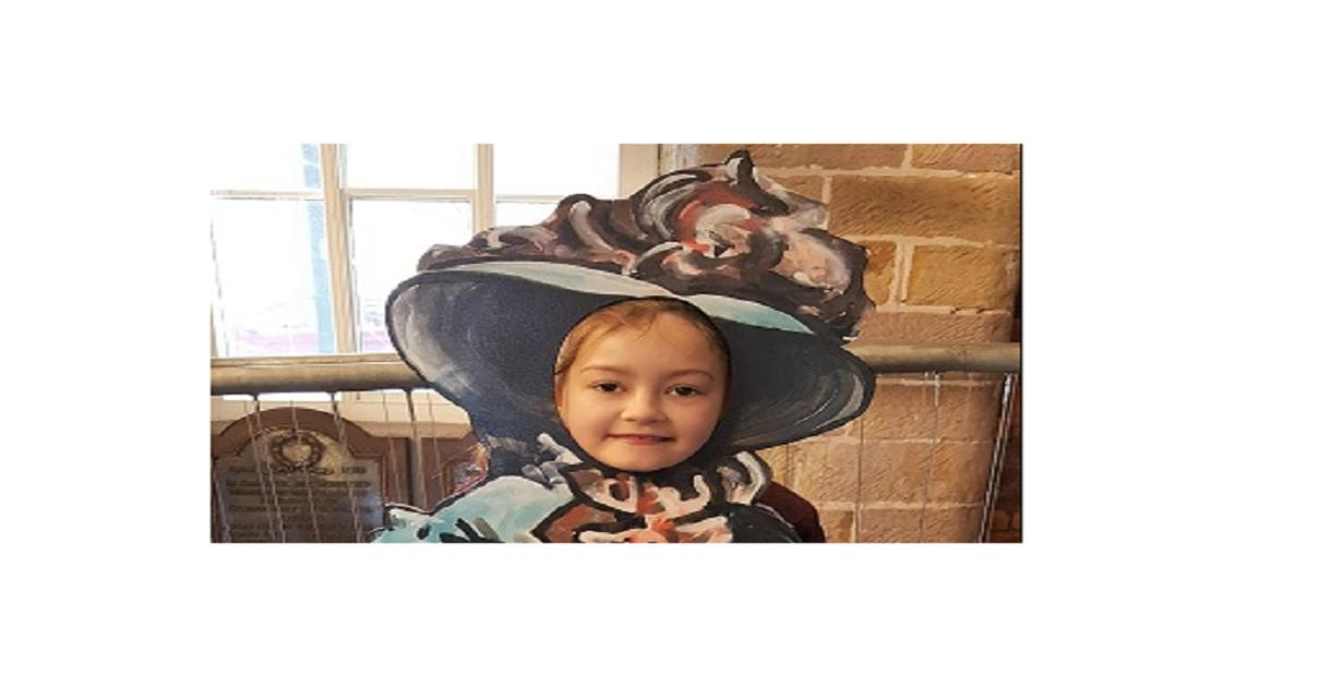 A girl standing posing with her head through the face hole of a cardboard cut out of a Victorian dressed child.